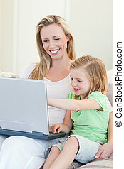 Mother and daughter with laptop on couch