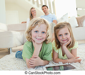 Children on the carpet with tablet and parents behind them -...