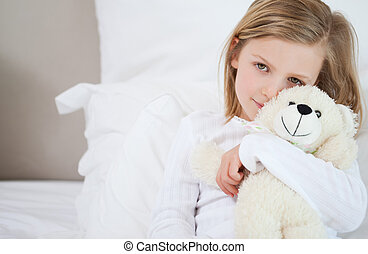 Girl with her teddy sitting on the bed - Little girl with...