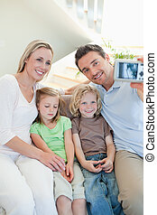 Man taking family picture on couch