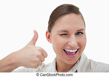 Businesswoman with the thumb up while winking against a...