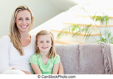 Mother and daughter sitting on couch together