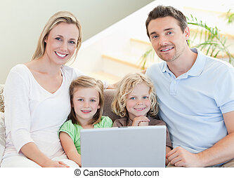 Family with laptop on the sofa