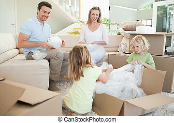 Family unpacking cardboard box in the living room together