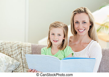 Mother and daughter reading a magazine on the sofa