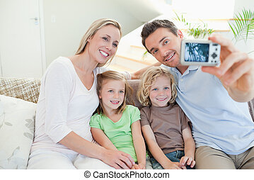 Father taking family picture on sofa