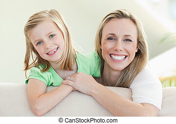 Smiling mother and daughter on the sofa - Smiling mother and...