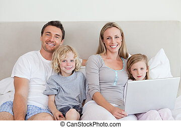 Family sitting on the bed with laptop