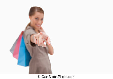 Hand of woman with shopping bags pointing against a white...