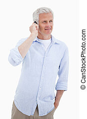 Portrait of a smiling mature man using his mobile phone...