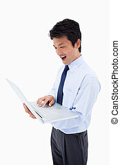 Portrait of a surprised businessman using a laptop