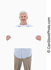 Portrait of a mature man holding a blank panel against a...