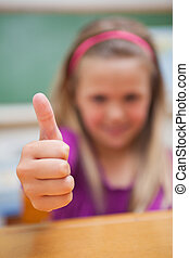 Portrait of a cute schoolgirl with the thumb up
