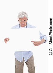 Portrait of a mature man pointing at a blank board against a...
