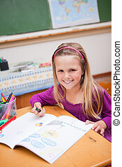 Portrait of a smiling schoolgirl drawing