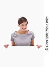 Smiling woman looking over blank wall against a white...