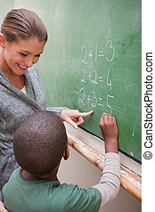 Portrait of a beautiful teacher and a pupil making an addition