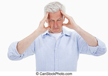 Tired man having a headache against a white background
