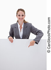 Smiling bank employee pointing down at blank sign