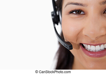 Smiling female call center agent with headset against a...