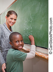 Portrait of a teacher explaining mathematics to a pupil on a...