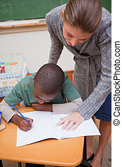Portrait of a teacher explaining something to a focused schoolboy in a classroom