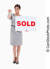 Woman with sold sign handing over key against a white...