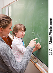 Portrait of a teacher and a pupil making an addition