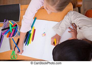 Above view of schoolgirls drawing