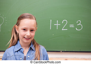 Schoolgirl standing up in front of a blackboard