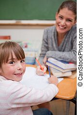 Portrait of a smiling teacher explaining something to her pupil