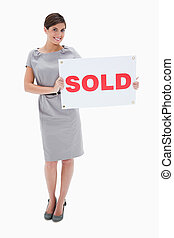 Woman holding sold sign in her hands against a white...