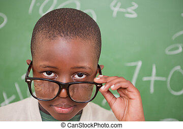 Schoolboy looking over his glasses