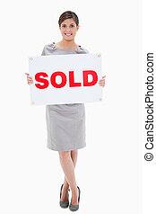 Woman holding sold sign against a white background