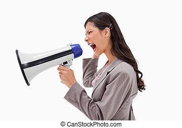 Side view of angry businesswoman yelling through megaphone...