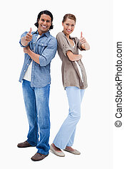 Smiling couple giving thumbs up against a white background