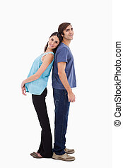 Portrait of a young couple standing back to back