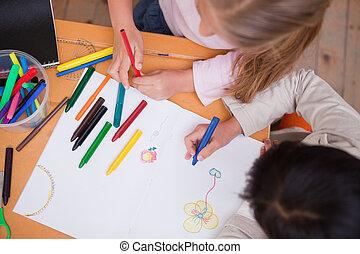 Above view of little schoolgirls drawing