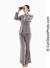 Portrait of a brunette businesswoman looking through binoculars