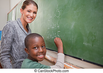 Smiling teacher and a pupil making an addition on a...