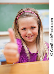 Portrait of a schoolgirl with the thumb up