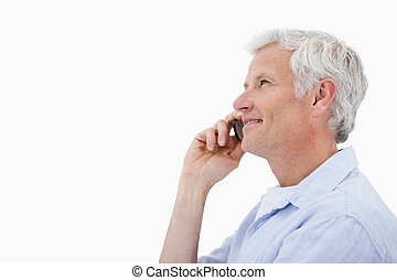 Side view of a smiling mature man making a phone call...