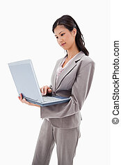 Side view of businesswoman standing with laptop