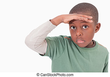 Boy putting his hand on his forehead against a white...