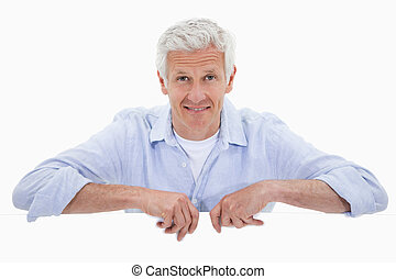 Portrait of a smiling mature man standing behind blank panel...
