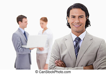 Smiling businessman with colleagues working on laptop behind him against a white background