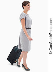 Side view of woman with wheely bag