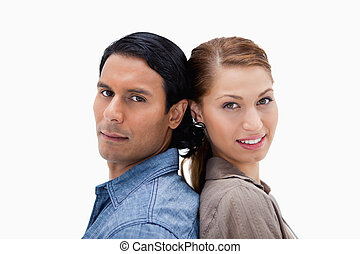 Side view of young couple standing back to back