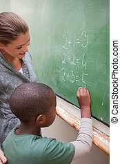 Portrait of a smiling teacher and a pupil making an addition