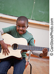 Portrait of a schoolboy playing the guitar
